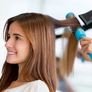 Woman getting her long hair blowed dried and styled