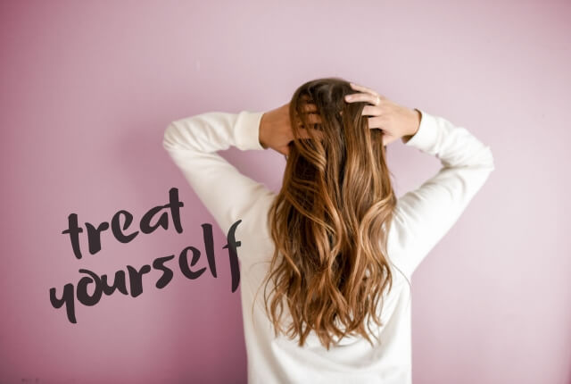 woman with long hair facing away on pink background - text says treat yourself